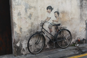 A street art picture in Penang of a little girl riding an adult bike with her brother on the back. The bike is partially painted on to the wall and partially 3D with half the handlebars and basked coming out of the wall.