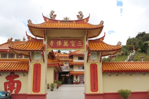 the entrance to the temple has cream walls and red signage and is topped with a pergola roof with shining orange tiles