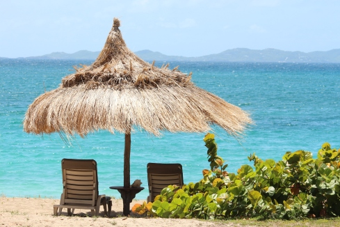 large straw umbrella nestled in the sand at Bequia Beach Hotel on the island of Bequia in the Grenadines with two sun loungers looking out to turquoise waters