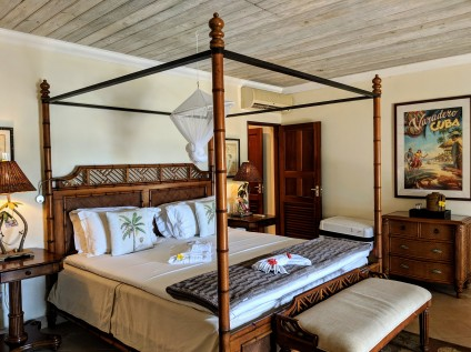 a beachfront junior suite with four poster bed at Bequia Beach Hotel